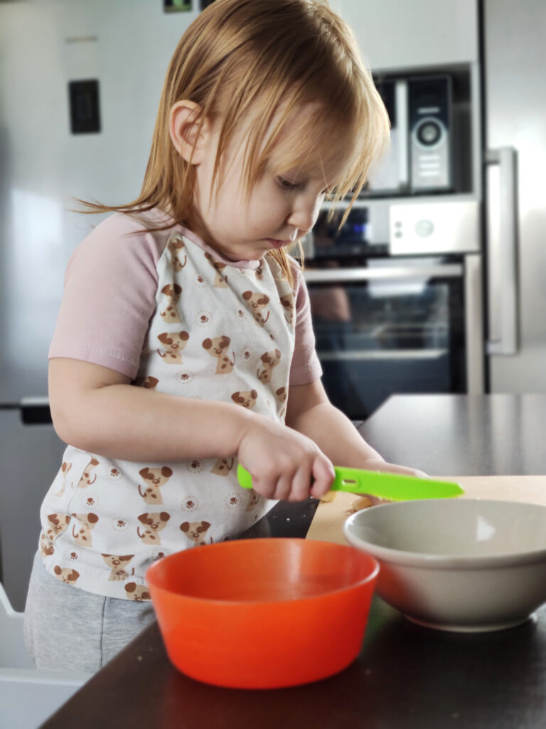 Dziecko kroi banana plastikowym nożem