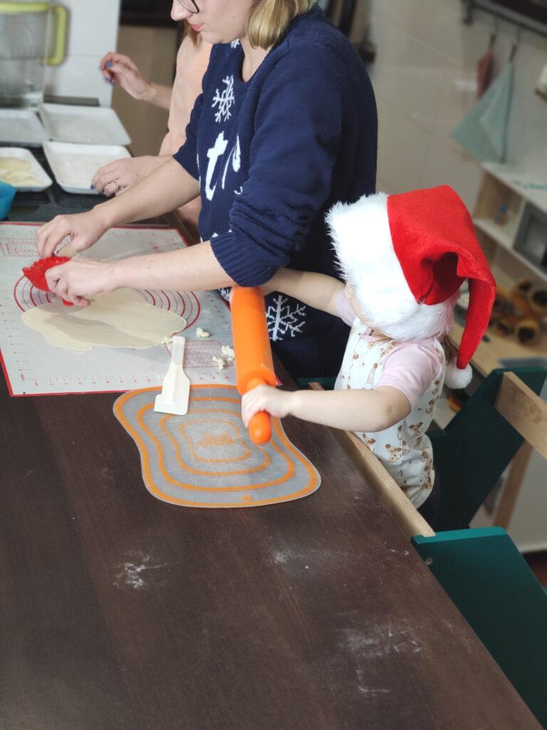 Dziecko stoi na kitchen helperze i trzyma wałek do ciasta, obok kobieta wycina pierogi