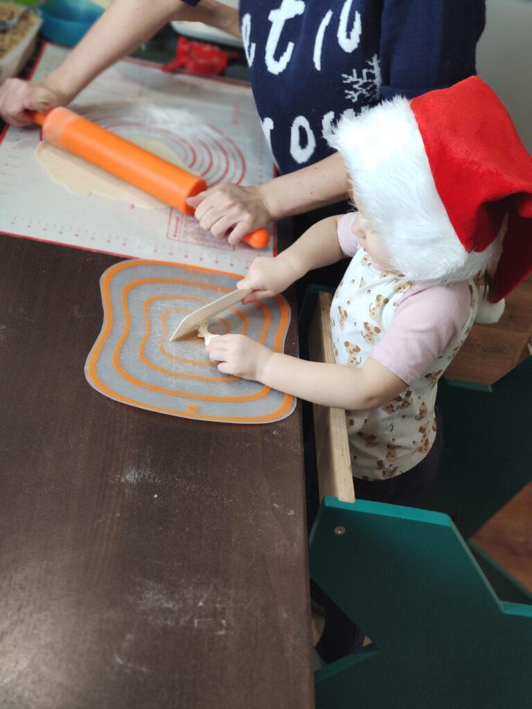 Dziecko kroi ciasto plastikowym nożem