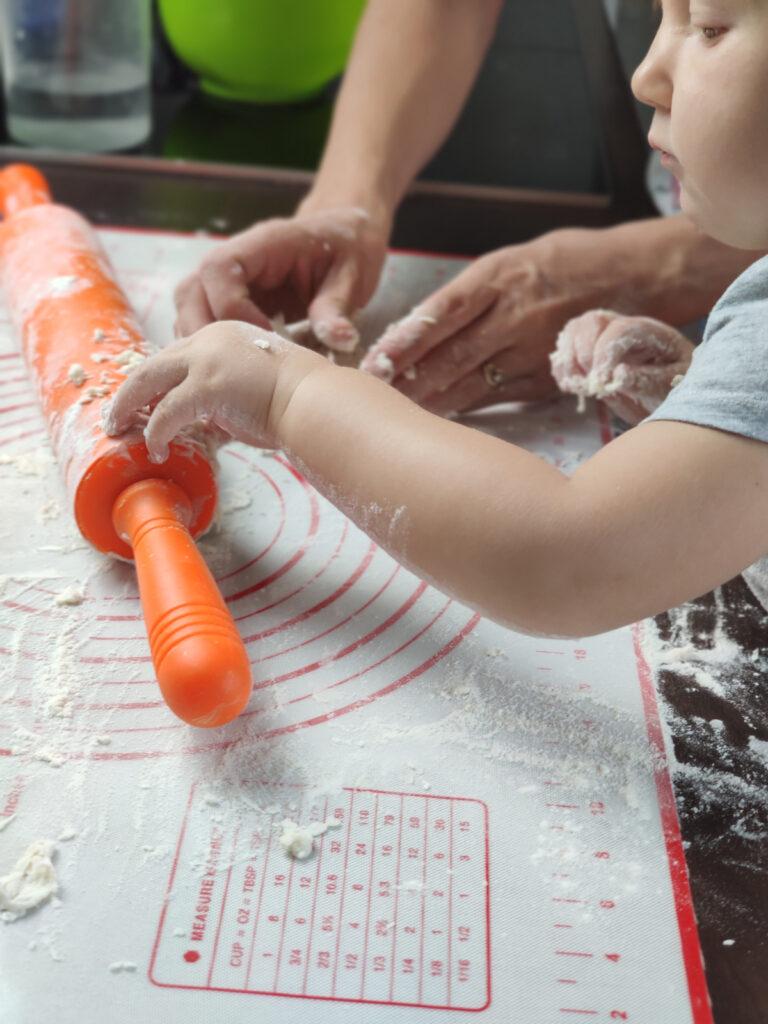 Dziecko trzyma wałek do wałkowania ciasta