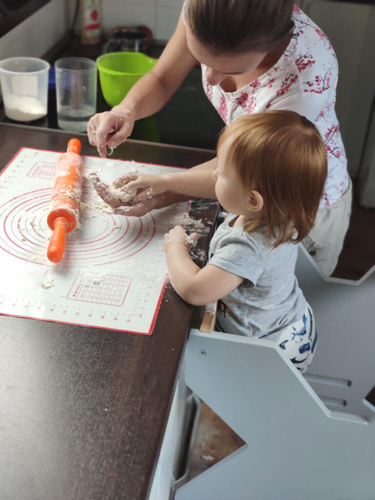 Mama trzyma w ręku ciasto, dziecko stoi na kitchen helperze i podaje mamie więcej ciasta