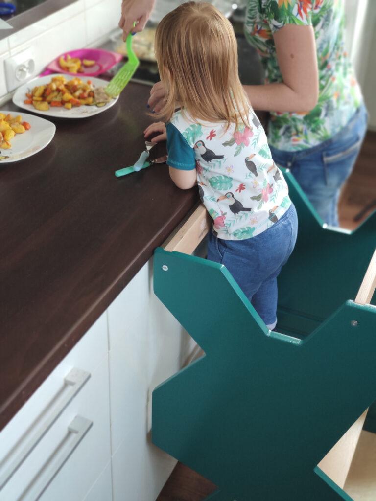 Mama stoi przy blacie i nakłada obiad na talerze, dziecko stoi na kitchen helperze i patrzy, co robi mama